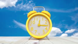 Yellow clock on table and sky time lapse on the bright sky.
