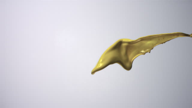 CU SLO MO Yellow colored liquid splashing in air