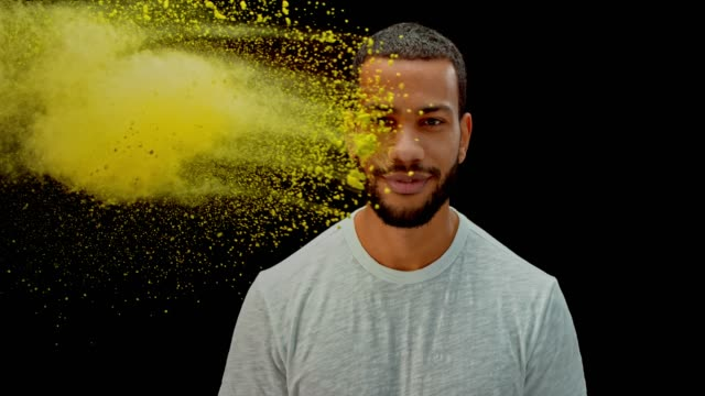 slo mo yellow colored powder hitting a young man into the face from the side - powder paint stock videos & royalty-free footage