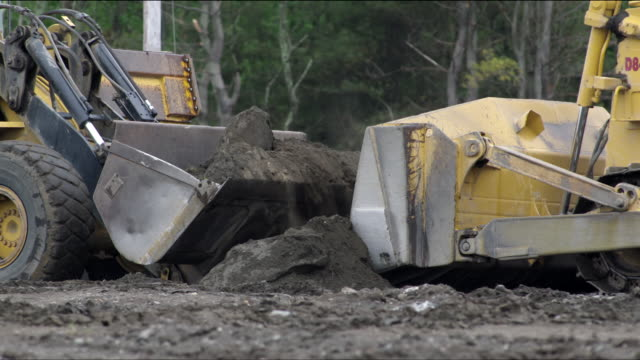 yellow construction front-end loader truck (bulldozer) scooping up a load of dirt and dumping it into a large articulated dump truck - bulldozer stock videos and b-roll footage