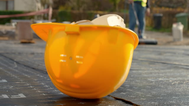 Yellow construction helmet falling onto the ground at the construction site