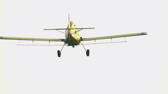 a yellow crop duster flies in a pale sky. - landefahrwerk stock-videos und b-roll-filmmaterial