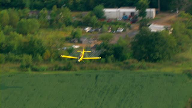 vídeos y material grabado en eventos de stock de a yellow crop duster sprays crops with pesticide. - insecticida