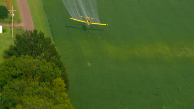 a yellow crop duster sprays crops with pesticide. - crop sprayer stock videos and b-roll footage