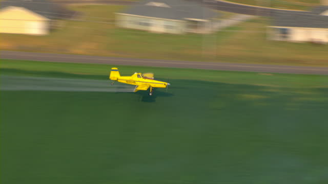 a yellow crop duster sprays crops with pesticide. - insecticide stock videos & royalty-free footage