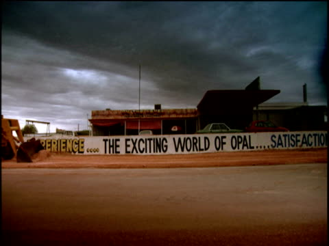 yellow digger drives along dusty car track smoothing the sand advertisement boards and cars in background coober pedy - coober pedy stock videos & royalty-free footage
