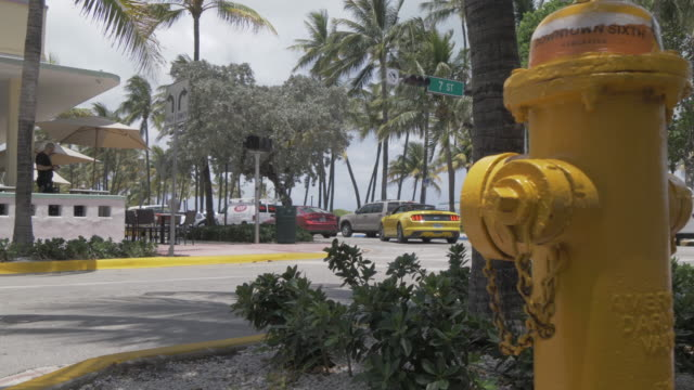 Yellow fire hydrant and traffic and people passing on Ocean Drive, South Beach, Miami, Florida, United States of America, North America