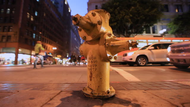 yellow fire hydrant with city intersection behind - fire hydrant stock videos & royalty-free footage
