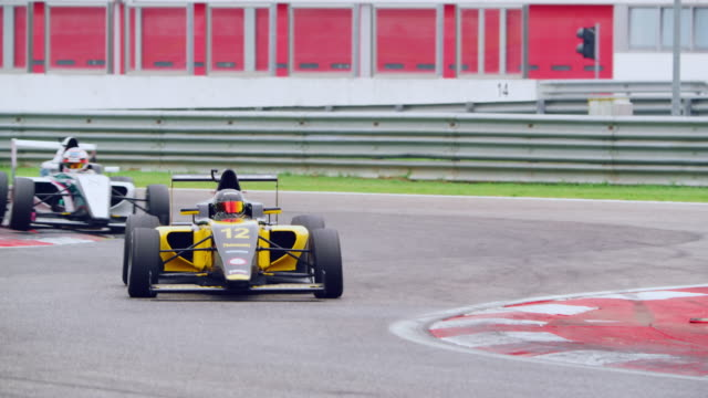 yellow formula in lead driving through the chicane - crash helmet stock videos & royalty-free footage