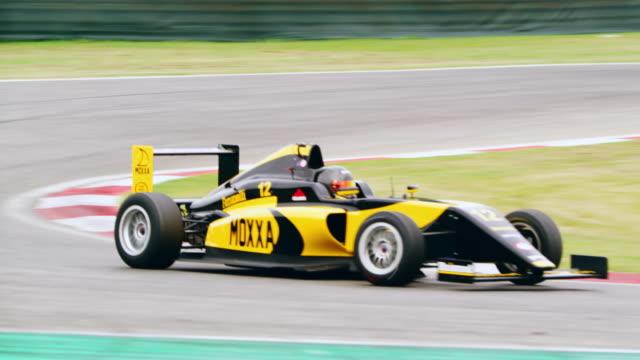 yellow formula racing on the track - 曲線点の映像素材/bロール