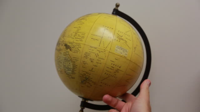 A yellow globe spins against a white wall