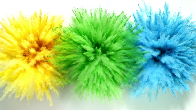 yellow, green and blue colored powder exploding towards camera at the same time in close up and super slow-motion, white background - three objects stock videos & royalty-free footage
