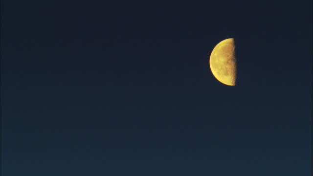 ms, yellow half moon against dark blue sky - half moon stock videos & royalty-free footage