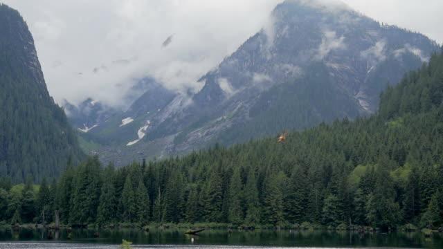 vídeos de stock, filmes e b-roll de yellow helicopter flying towards mountain valley in vancouver, canada - grosso