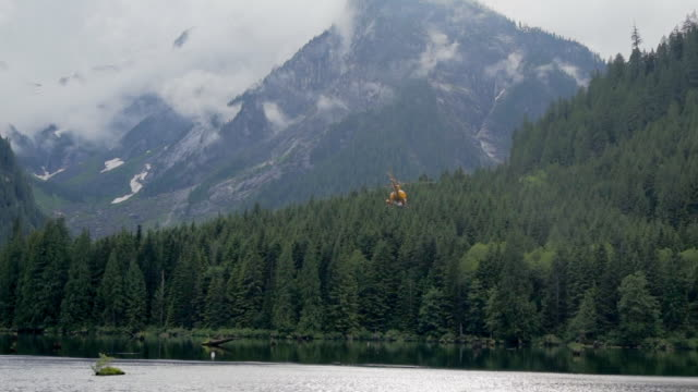 yellow helicopter leaving mountain lake in vancouver, canada - british columbia stock videos & royalty-free footage