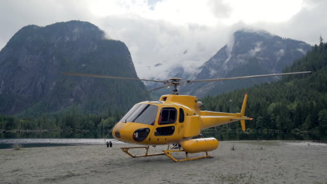 vidéos et rushes de yellow helicopter ready to leave shore of mountain lake in vancouver, canada - pare brise