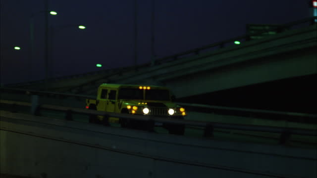 ms pan yellow hummer moving on freeway at night - hummer stock-videos und b-roll-filmmaterial