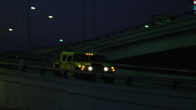 vídeos y material grabado en eventos de stock de ms pan yellow hummer moving on freeway at night - hummer