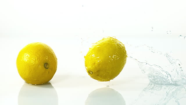 yellow lemons, citrus limonum, fruits falling into water and splashing against white background, slow motion 4k - lemon stock videos & royalty-free footage