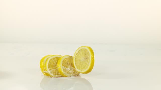 yellow lemons, citrus limonum, fruits falling into water and splashing against white background, slow motion 4k - 四つ点の映像素材/bロール