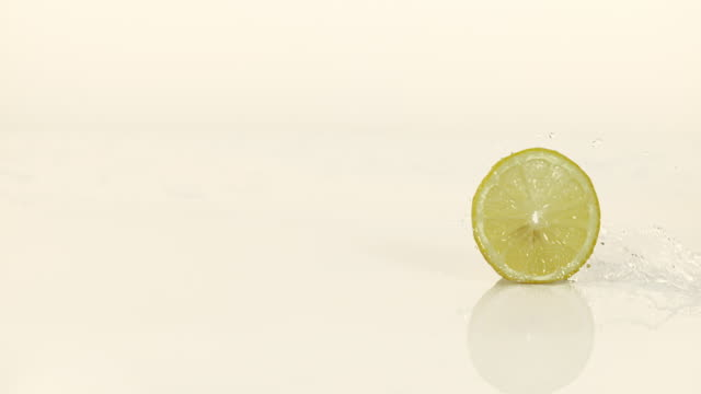 Yellow Lemons, citrus limonum, Fruits falling into Water and splashing against White Background, Slow Motion 4K