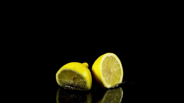 yellow lemons, citrus limonum, fruits falling on water and splashing against black background, slow motion - lemon stock videos & royalty-free footage