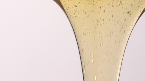 vídeos y material grabado en eventos de stock de (cámara lenta) líquido amarillo vertido sobre fondo blanco - miel