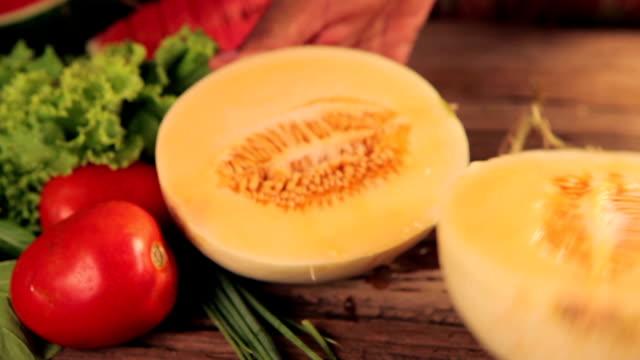 vídeos de stock, filmes e b-roll de fatias de melão amarelo com forma de coração na mão feminina - melão musk