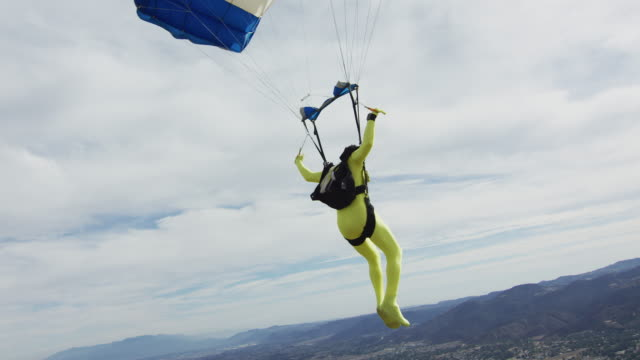 yellow morph suit skydiver flies parachute - fancy dress costume stock videos & royalty-free footage