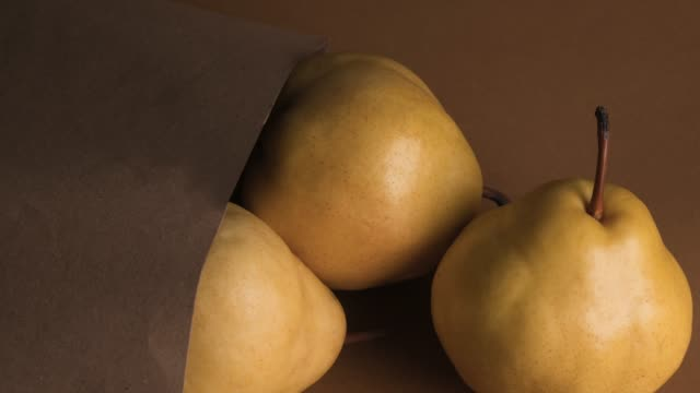 yellow pear in paper shopping bag over brown background - ripe stock videos & royalty-free footage