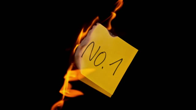 slo mo ld yellow piece of paper with inscription 'no. 1' burning in flames - number 1 stock videos & royalty-free footage