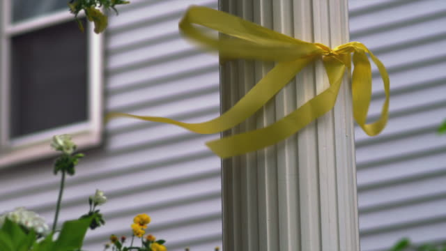 vidéos et rushes de cu yellow ribbon blowing in wind on column in front of house/ chicago, il - noeud ruban