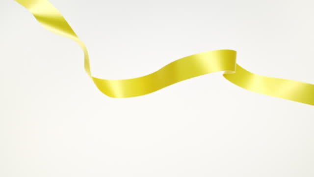 a yellow ribbon on white background, for celebration events and party for new year, birthday party, christmas or any holidays, waiving and curling in super slow motion and close up - banner sign stock videos & royalty-free footage