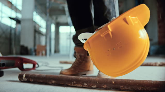 vídeos de stock e filmes b-roll de slo mo yellow safety helmet being falling on the ground at the construction site - proteção