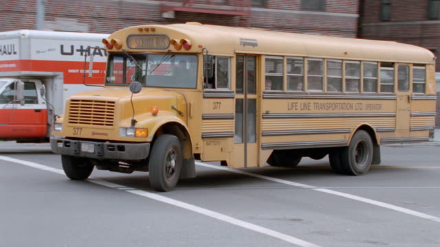 a yellow school bus drives around a corner on a new york street. - 2001 stock videos & royalty-free footage