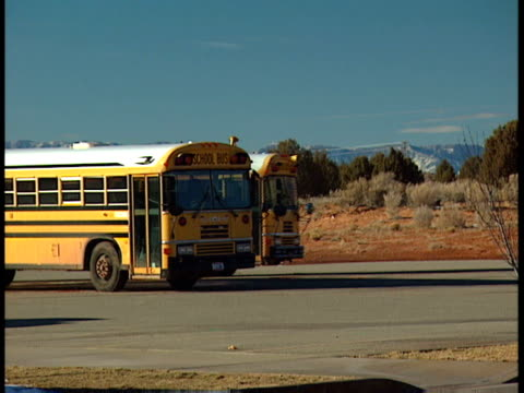 yellow school bus parked in parking lot second yellow bus pulling up next to it parking also elementary kindergarten public school junior high school... - field trip stock videos & royalty-free footage