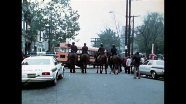 of yellow school bus passes by a group of mounted police officers blocking the road during the desegregation busing crises in boston, usa; 1974. - 1974 bildbanksvideor och videomaterial från bakom kulisserna