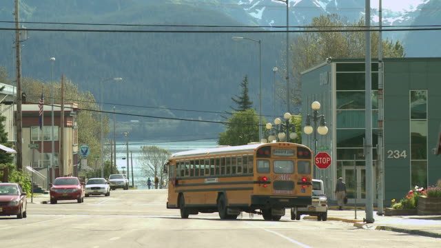 """Yellow school bus pulls out from stop and turns right at intersection of Adams Street and 4th Avenue, shot from corner of Adams Street and 3rd Avenue, Seward, Kenai Peninsula, Alaska."""