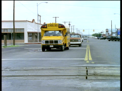 Yellow school bus waits to go over level crossing bar comes up and bus moves along road towards camera.