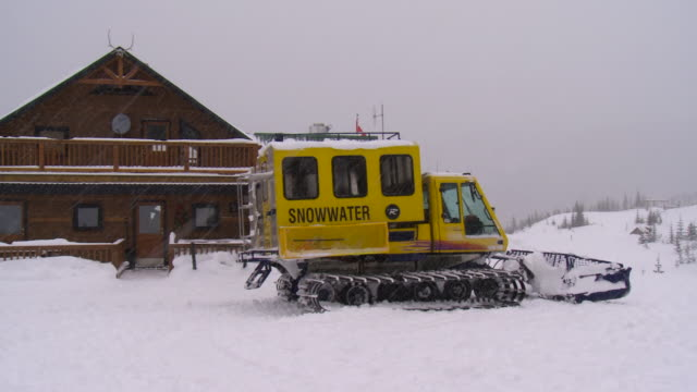 yellow 'snowwater' snow tractor parked in front of ski lodge on overcast snowy day in the selkirk mountains - ski lodge stock videos & royalty-free footage