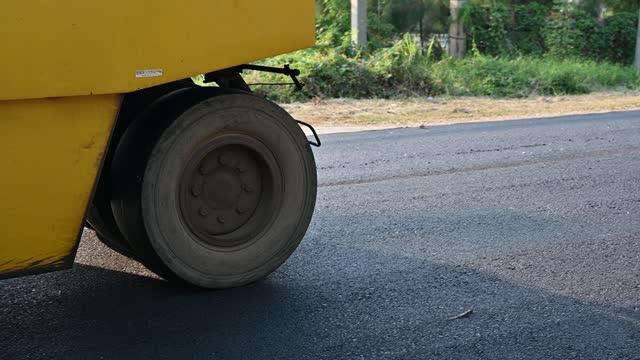 vídeos de stock e filmes b-roll de yellow steamroller or soil compactor working on asphalt road at construction site - cilindro veículo terrestre comercial