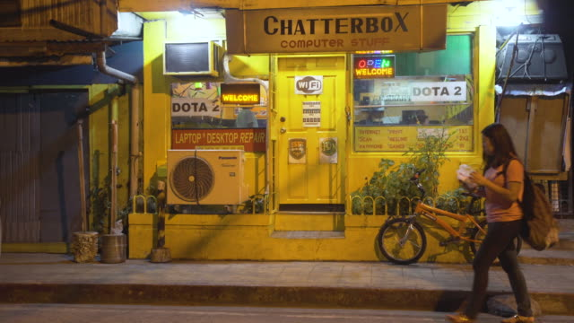 yellow store front at manila. iconic it business named computer stuff. makati district at night. philippines - it support stock videos & royalty-free footage