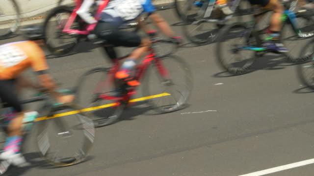 yellow stripe in road, racing in a road bike bicycle race. - slow motion - プロトン点の映像素材/bロール