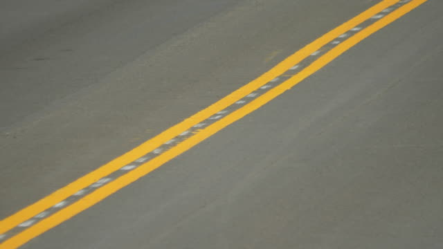 a yellow stripe in the middle of a striped road street. - slow motion - striped stock videos & royalty-free footage
