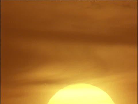 yellow sun rises into orange sky, mauritania - モーリタニア点の映像素材/bロール