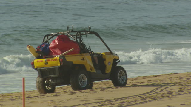 yellow 'surf rescue' dune buggy stationary on the sand with the surf rolling in in the background 'surf rescue' dune buggy driving along the sand... - dune buggy stock videos and b-roll footage