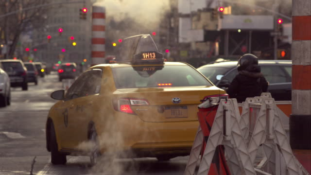 vidéos et rushes de yellow taxi cab and motorcycle waiting for green light on new york city street. steam rises from manhole. - yellow taxi