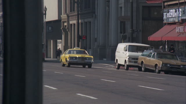 ms pan yellow taxi cab approaching corner to theater on business street - gelbes taxi stock-videos und b-roll-filmmaterial