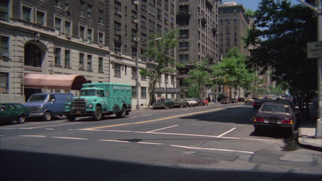 ms ts pan yellow taxi cab moving on road at apartment building area - anno 1983 video stock e b–roll