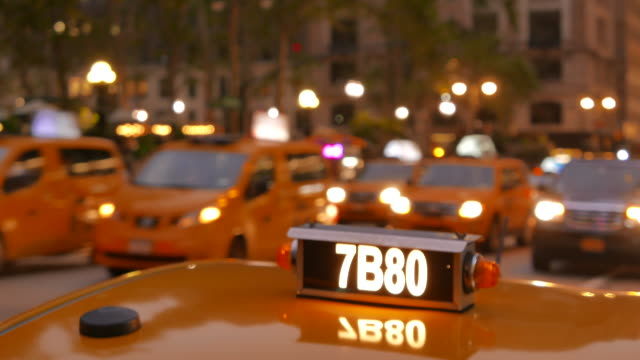 yellow taxi car in new york city at night. close up of taxi roof light. traffic and transportation background